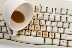 Coffee and damaged computer keyboard stock photos