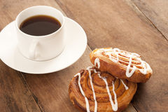 Coffee with Danish pastries. Freshly brewed full roast cup of filter or espresso coffee served with flaky fruity Danish pastries drizzled with icing sugar for a Stock Image