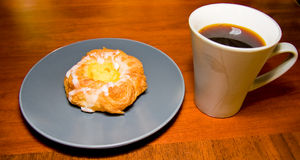 Coffee and Danish pastry. Danish Pastry on gray blue plate with cup of hot black coffee on a brown wooden table Royalty Free Stock Images