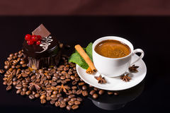 Coffee with Dark Chocolate Cake and Roasted Beans. High Angle Still Life View of Frothy Gourmet Espresso Coffee Garnished with Fresh Mint Leaves, Cinnamon Stick Stock Photo