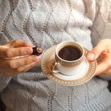 Coffee and dates. A Cup of coffee in her hands with the Arabic dates. royalty free stock image