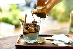 Coffee and dessert, Pouring coffee drink in sweet ice-cream affogato. royalty free stock image