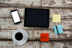 Coffee, digital table, smartphone and sticky notes on wooden table Stock Image