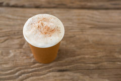 Coffee in disposable cup on wooden table Royalty Free Stock Photography