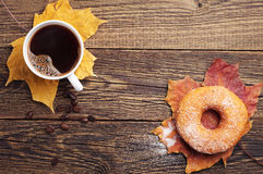 Coffee, donut and autumn leaves Stock Image