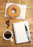 Coffee with donut and notepad Stock Images
