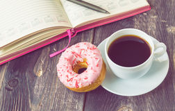 Coffee, donut and notepad on wooden background. Black coffee, donut covered with pink icing and notepad on a rustic wooden background. Vintage toned picture Stock Photos
