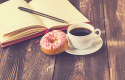Coffee, donut and notepad on wooden background. Black coffee, donut covered with pink icing and notepad on a rustic wooden background. Vintage toned picture Stock Image