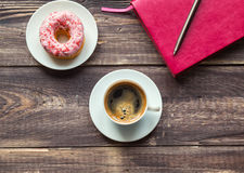 Coffee, donut and pink notepad on wooden background Stock Photography