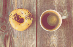 Coffee and donut on wooden background. Espresso coffee and donut on a rustic wooden background. Top view. Vintage toned picture Royalty Free Stock Photography