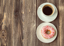 Coffee and donut on wooden background. Espresso coffee and donut on a rustic wooden background. Top view. Vintage toned picture Royalty Free Stock Photos