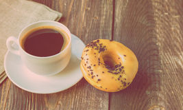 Coffee and donut on wooden background. Espresso coffee and donut on a rustic wooden background. Vintage toned picture Royalty Free Stock Photos