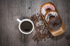 Coffee and donut on the wooden table. Box of donut with cup of fresh coffee and coffee beans on the wooden table Stock Photography