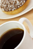 Coffee and Doughnut. Mug of black coffee and doughnut in abstract macro close up Stock Image
