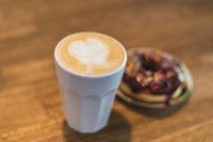Coffee with a drawn heart and milk on a wooden table in a coffee shop. chocolate donut with scattering on the table next to the royalty free stock photo