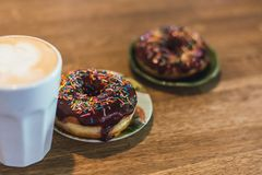 Coffee with a drawn heart and milk on a wooden table in a coffee shop. two chocolate donuts with scattering on the table next to stock photography