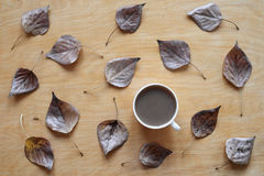 Coffee and dried leaves on wooden background Stock Photos