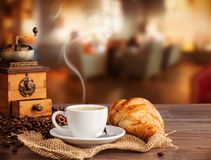 Coffee drink in cafeteria. Coffee drink served with croissant on wooden table with blur cafeteria as background Royalty Free Stock Images