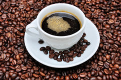 Coffee drink and coffee beans. A cup of coffee with coffee beans as background Stock Photography
