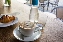 Coffee drink served with croissant on wooden table with blur str Stock Photography