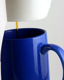 Coffee drip and blue mug. Bright cobalt blue mug under coffee maker drip royalty free stock photos
