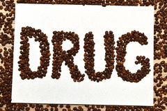Coffee is drug. Coffee addiction as drug. Word Drug made of coffee beans on white canvas horizontal. Flat Stock Photo