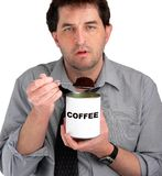Coffee Eater. Tired, dishevelled business man eating coffee from the can royalty free stock images