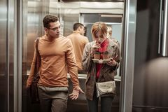 Slim blonde-haired girlfriend drinking coffee in the elevator stock photos