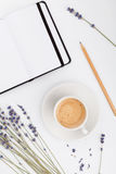 Coffee, empty notebook and lavender flower on white  background from above. Woman working desk. Cozy breakfast. Mockup. Flat lay. Stock Photo