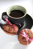 Coffee Espresso and Cookie Treat. Image of an espresso coffee with two chocolate cookies wrapped in pink bows royalty free stock image