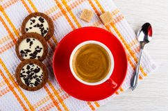 Coffee in cup, cookies with cream and chocolate, sugar, spoon on napkin on table. Top view. Coffee espresso in red cup, round cookies with cream and chocolate royalty free stock photography