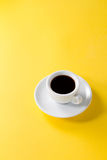 Coffee espresso in small white ceramic cup on yellow vibrant bac Stock Photos
