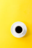 Coffee espresso in small white ceramic cup on yellow vibrant bac Royalty Free Stock Photo