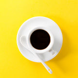 Coffee espresso in small white ceramic cup on yellow vibrant bac Royalty Free Stock Photos