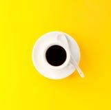 Coffee espresso in small white ceramic cup on yellow vibrant bac Stock Image