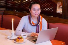 Coffee in the evening. Young Asian woman with a laptop sits at a table looking at camera. A burning candle, cake and a cup of coffee are on the table. Warm Stock Images
