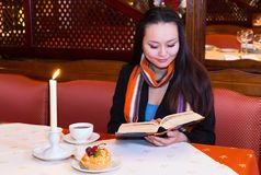 Coffee in the evening. Young Asian woman reads a book. A burning candle, cup of coffee and a cake are on the table. Warm evening indoors Stock Photo