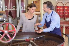 Coffee factory employee explaining roasting to female visitor. Explaining stock photography