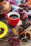 Coffee in the fall. Cup of black coffee on background with warm blanket strewn with autumn leaves Stock Image