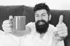 Coffee fills you with energy. Good gay begins from cup of coffee. Coffee affects body. Man handsome hipster relaxing on. Bed with coffee cup. Habits and rituals stock photography