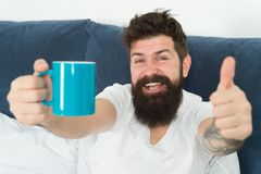 Coffee fills you with energy. Good gay begins from cup of coffee. Coffee affects body. Man handsome hipster relaxing on stock photos