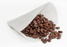Coffee Filter Full Of Whole Beans. Roasted coffee beans spill from paper coffee maker filter on white background Royalty Free Stock Images
