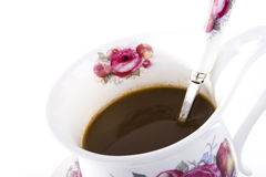 Coffee in floral mug. A mug of coffee with spoon on white background Stock Photography