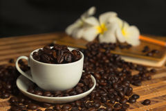Coffee flower background. Cup filled with coffee beans in the background flower royalty free stock photo