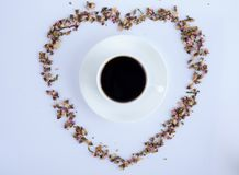 A cup of Black coffee and flowers with white background. View of a cup of black coffee and flowers with black background royalty free stock photo