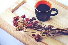 Coffee and flowers. A cup of coffee and flower on wooden board Royalty Free Stock Photos
