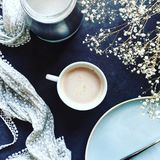 Coffee with flowers in style. Flatlay top view of a cup of coffee, small white flowers, floral scarf or foulard and sugar on black background. Spring coffee Stock Photo