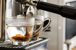 Coffee flowing into the cup. From coffee machine Royalty Free Stock Images