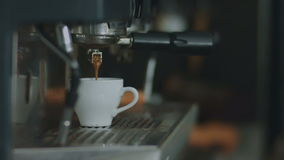 Coffee flows from the coffee machine in a mug stock video footage