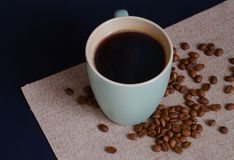 Strong Colombian coffee in a light green cup and whole coffee beans arabica. Top view. royalty free stock photography